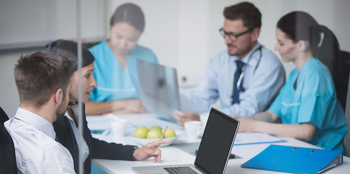 Doctors discussing over laptop in meeting at conference room